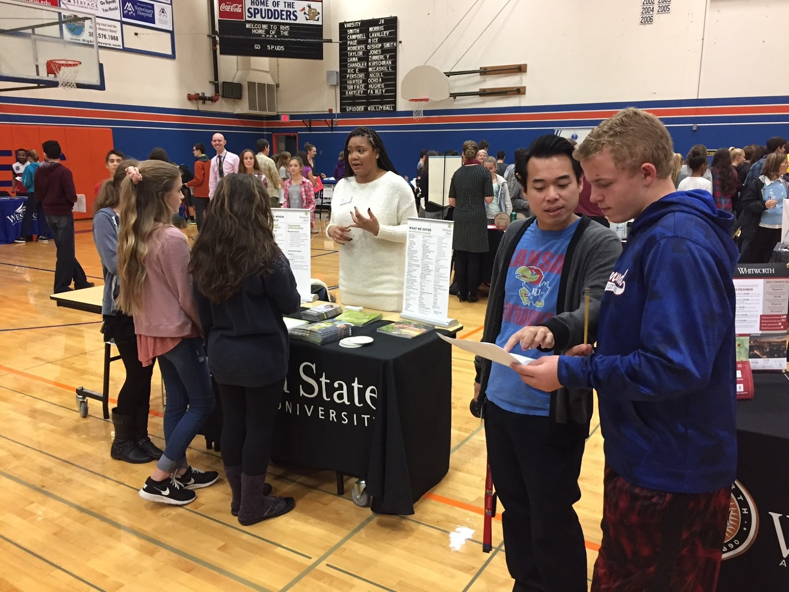 View Ridge Middle School student, Elijah Engstrom, consults with teacher, Nam Nguyen at the Fall College Fair.  In the background, students get information about Portland State University.